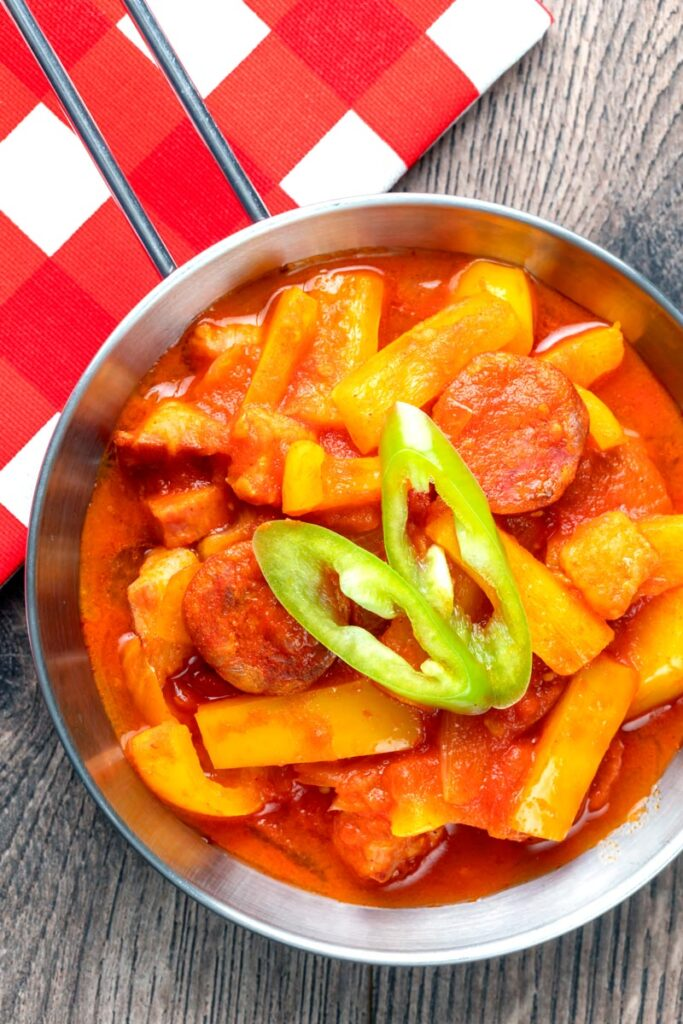 Portrait overhead image of a Hungarian Lecso, a tomato and pepper stew with salami and bacon