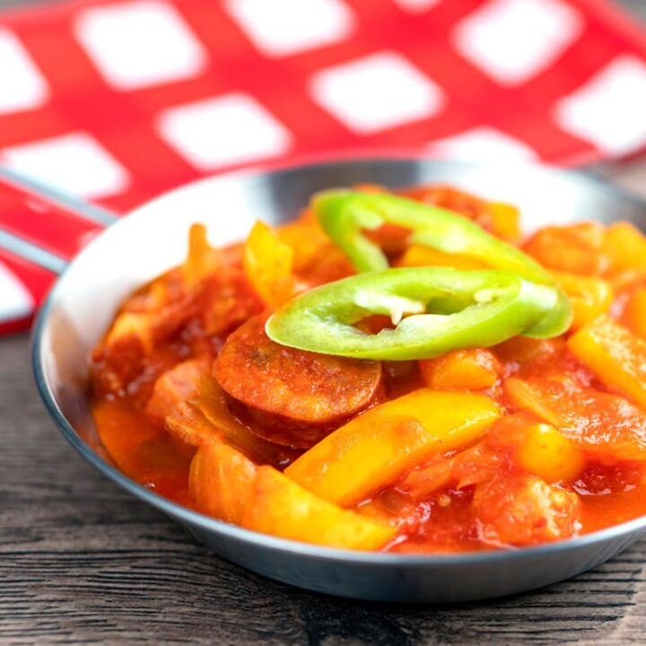 Square image of a Hungarian Lecso, a tomato and pepper stew with salami and bacon
