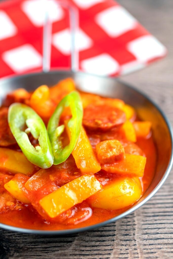 Portrait image of a Hungarian tomato and pepper stew with salami and bacon