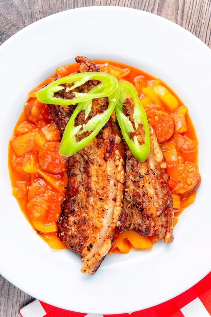 Portrait overhead image of a pork belly slices served on a hungarian tomato and pepper stew with salami and bacon