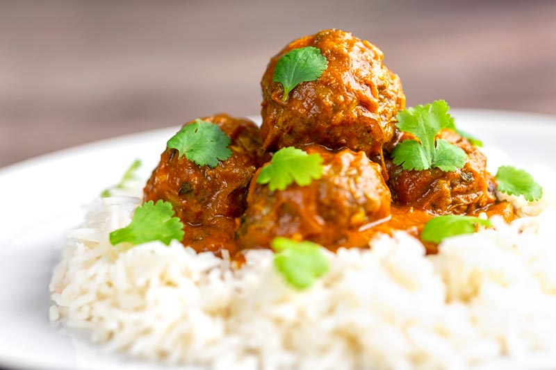 Landscape image of spicy venison meatballs served with basmati rice and coriander leaved