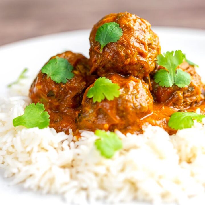 Square image of spicy venison meatballs served with basmati rice and coriander leaves