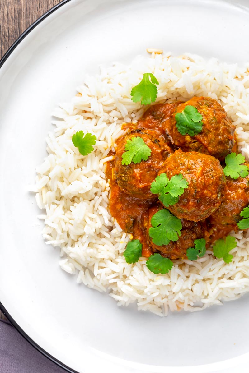 Portrait overhead image of spicy venison meatballs served with basmati rice and coriander leaves