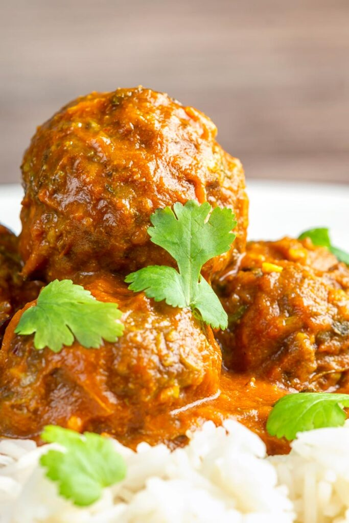 Portrait close up image of spicy venison meatballs served with basmati rice and coriander leaves