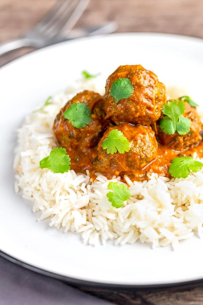 Portrait image of spicy venison meatballs served with basmati rice and coriander leaves
