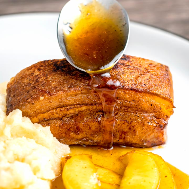 Square image of a sauce being poured from a spoon over Instant Pot Pork Belly served with apples and celeriac mash