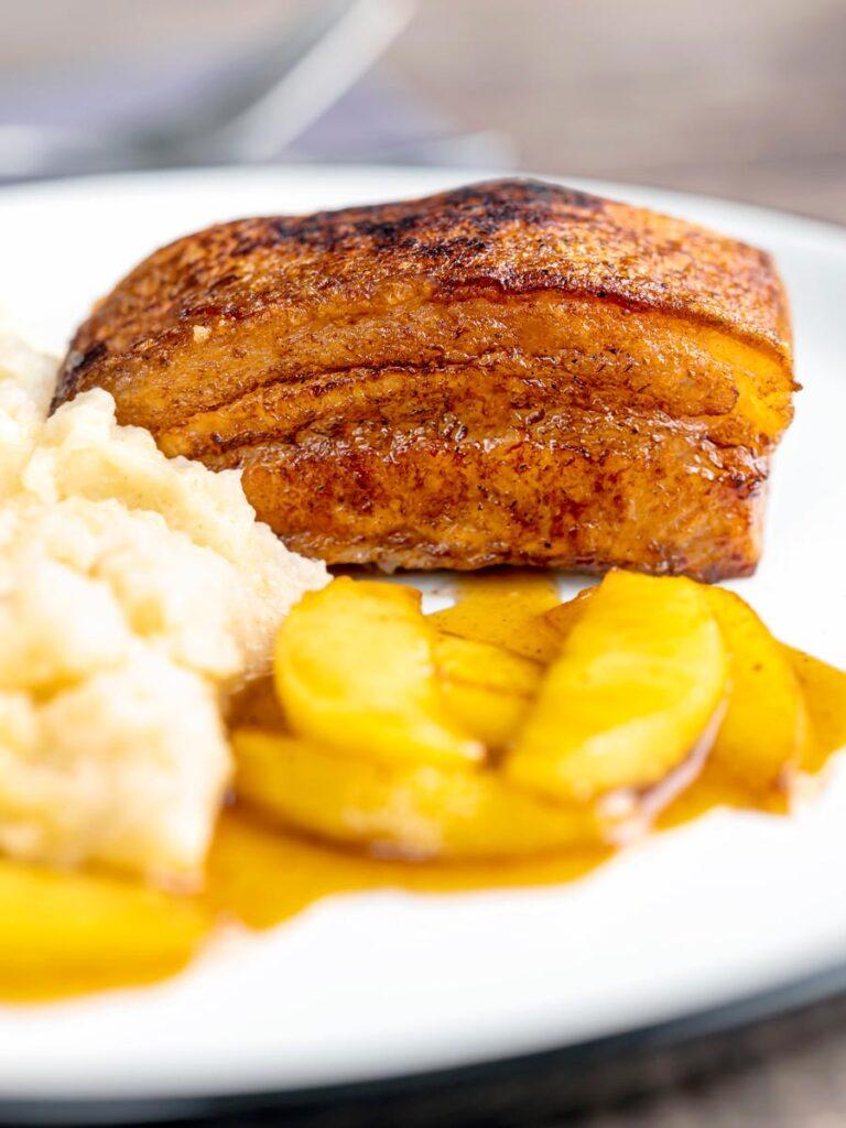 Portrait image of crispy Pork Belly served with apples and celeriac mash