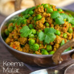 Portrait image of a keema matar minced lamb and pea curry serfved with coriander leaves in a karahi bowl with text overlay