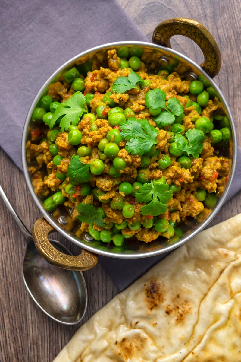 Portrait overhead image of a keema matar minced lamb and pea curry serfved with coriander leaves in a karahi bowl