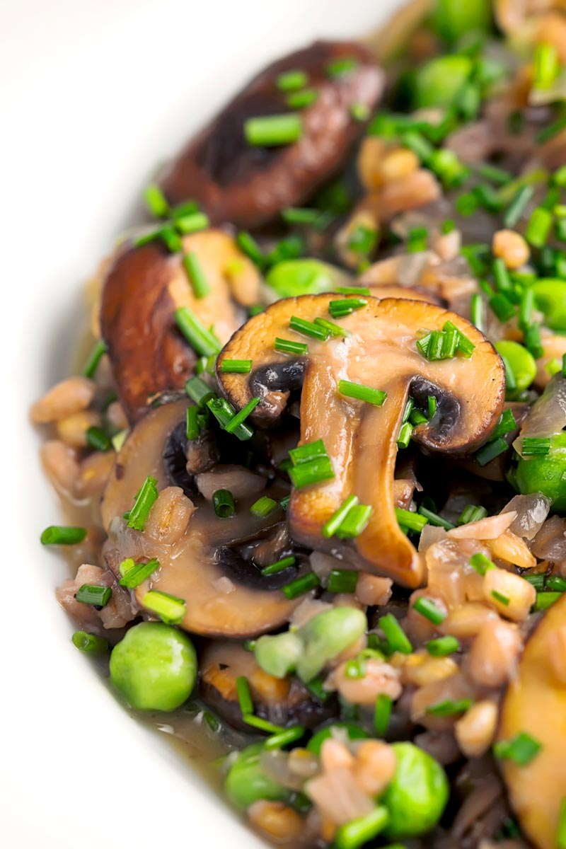 Portrait close up image of a Pea and Mushroom risotto made with pearl barley