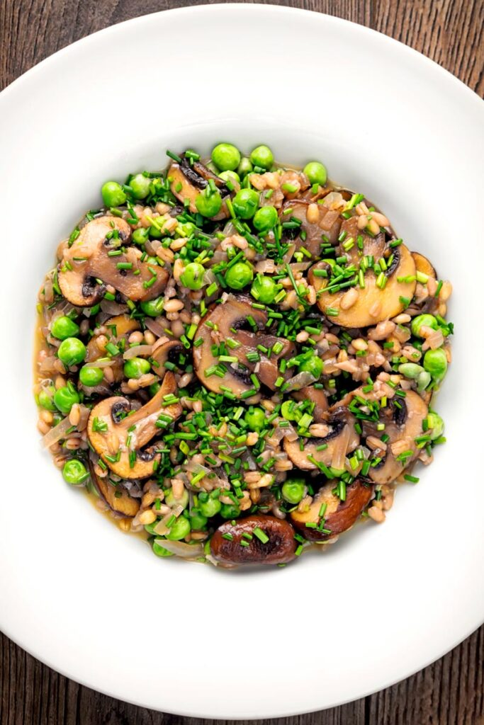 Portrait overhead image of a Pea and Mushroom risotto made with pearl barley