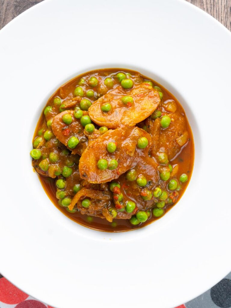 Portrait image of a pea and potato curry or aloo matar served in a white bowl