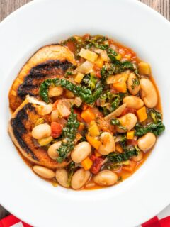 Portrait Overhead image of an Italian Ribollita stew featuring beans, cabbage, carrots, tomatoes and grilled bread