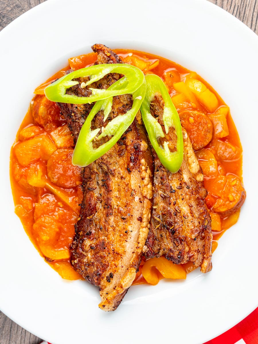 Portrait overhead image of roast pork belly slices served on a Hungarian lecso served in a white bowl