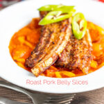 Portrait image of roast pork belly slices served on a Hungarian lecso served in a white bowl with text overlay