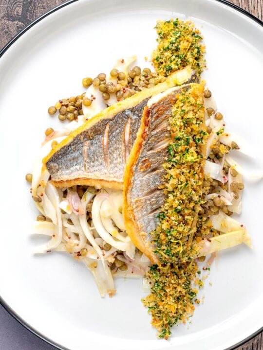 Portrait overhead image of pan fried sea bream fillet served with a parsley crumb and puy lentils with fennel