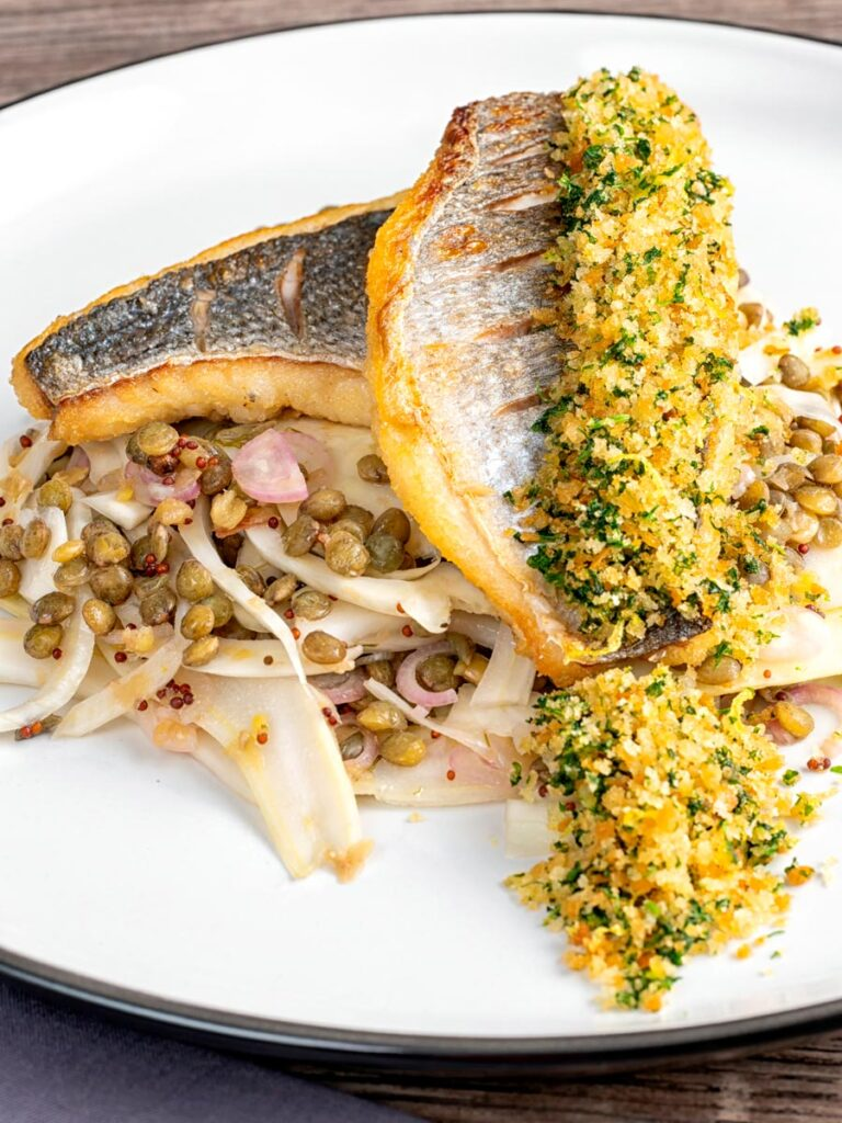 Portrait image of pan fried sea bream fillet served with a parsley crumb and puy lentils with fennel