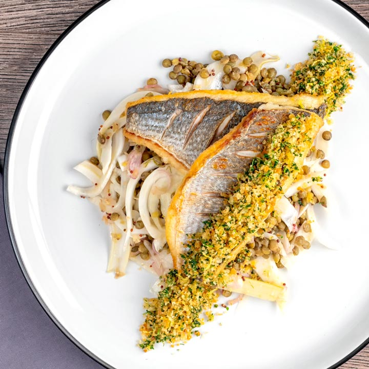 Square overhead image of pan fried sea bream fillet served with a parsley crumb and puy lentils with fennel