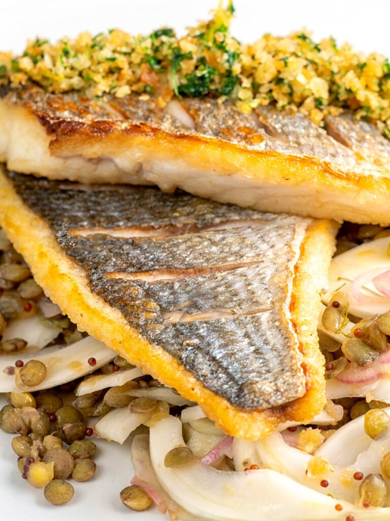 Portrait close up image of pan fried sea bream fillet served with a parsley crumb and puy lentils with fennel