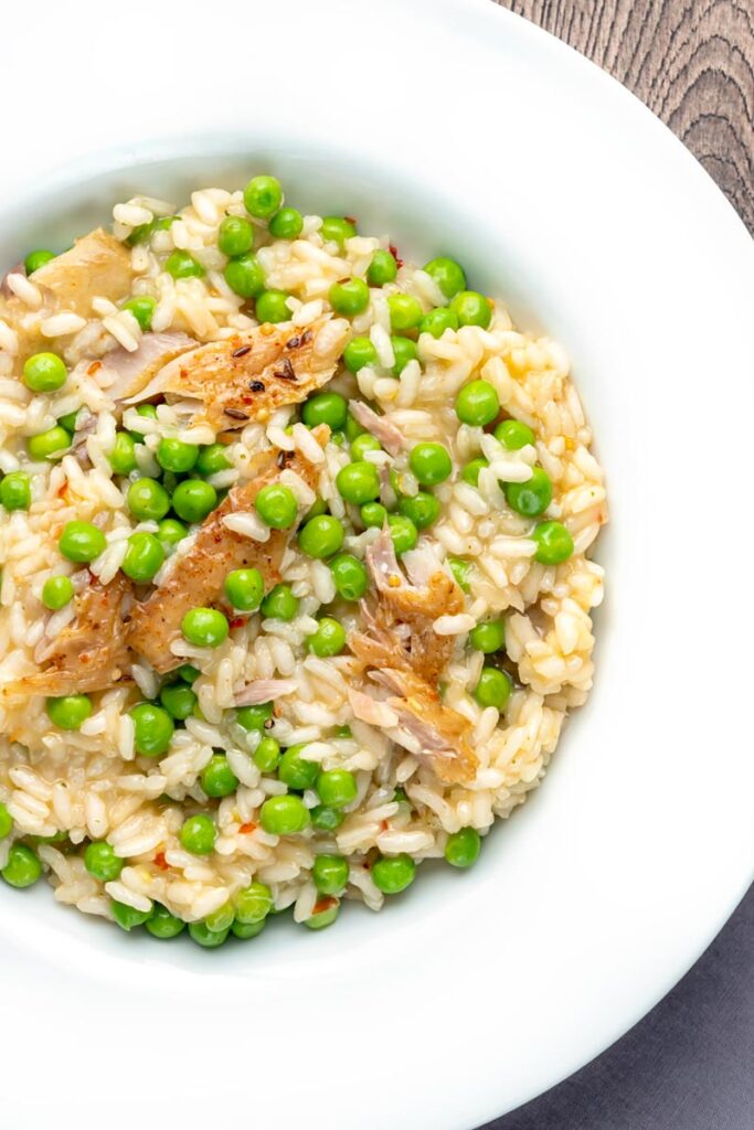 Portrait overhead image of a smoked fish risotto with peas served in a shallow white bowl