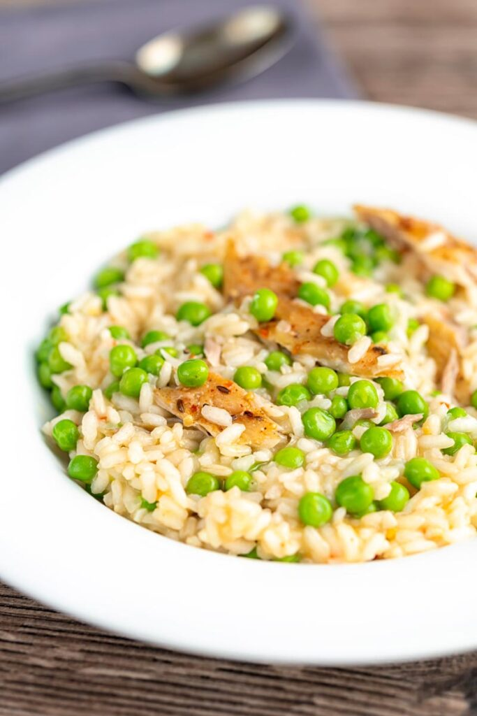 Portrait image of a smoked fish risotto with peas served in a shallow white bowl