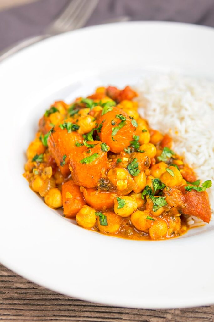 Portrait image of a chickpea and carrot curry served in a white bowl with rice and coriander