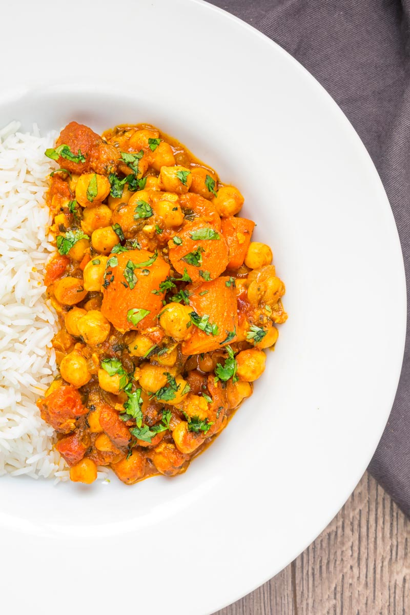 Portrait overhead image of a chickpea and carrot curry served in a white bowl with rice and coriander