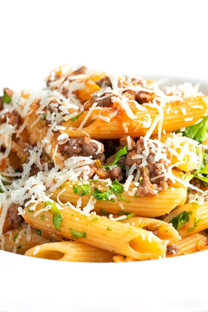 Portrait close up image of a bolognese style ragu served with penne pasta