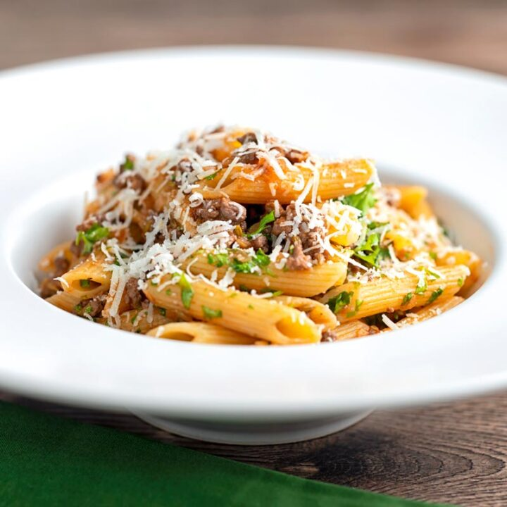 Square image of a wild boar ragu served with penne pasta in a white pasta bowl