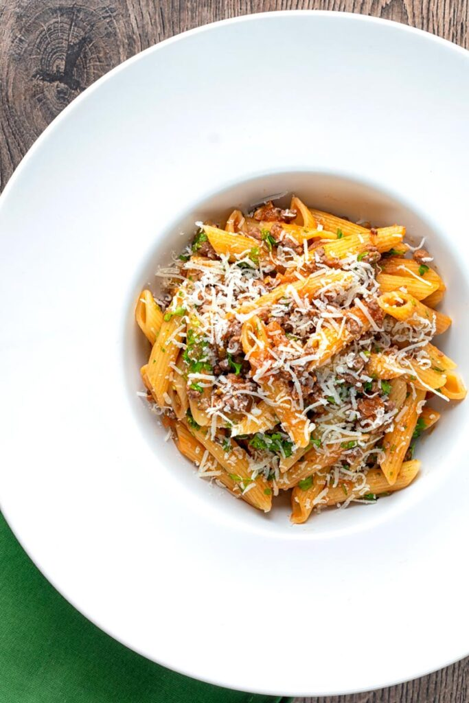 Portrait overhead image of a wild boar bolognese style ragu served with penne pasta