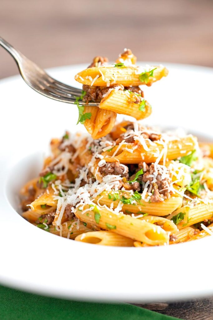 Portrait image of a bolognese style ragu served with penne pasta being eaten with a fork