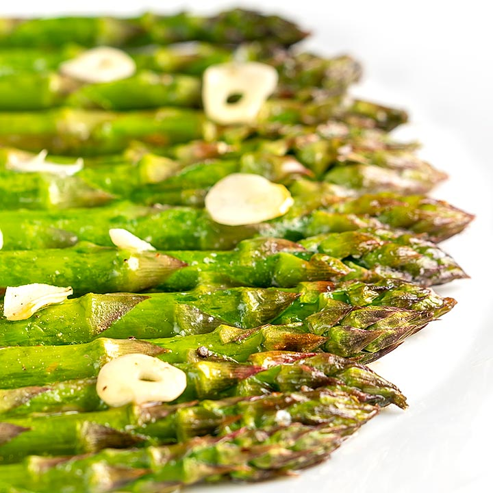 Square image of buttery air fryer cooked asparagus with garlic slices