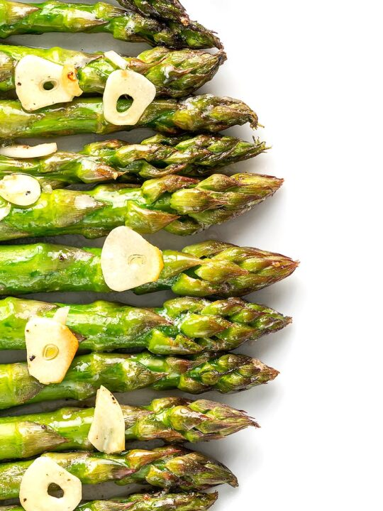 Portrait overhead image of buttery air fryer cooked asparagus with garlic slices