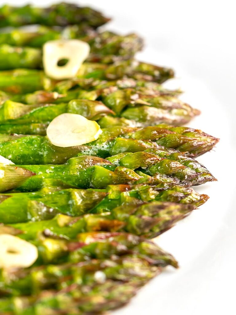 Portrait image of buttery air fryer cooked asparagus with garlic slices