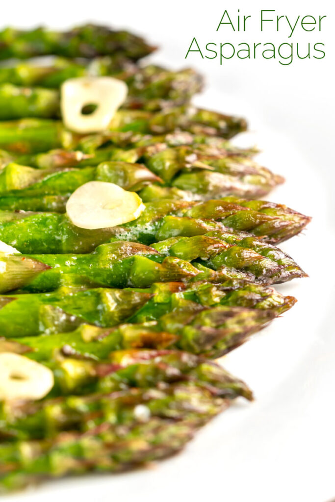 Portrait image of buttery air fryer cooked asparagus with garlic slices and a text overlay