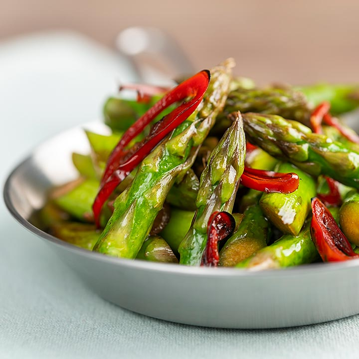 Square image of asparagus stir fry with chilli and garlic served in a small frying pan
