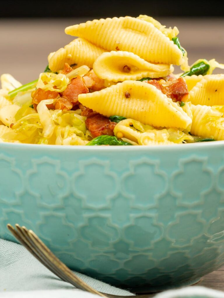 Portrait image of bacon and savoy cabbage pasta served in a baby blue bowl