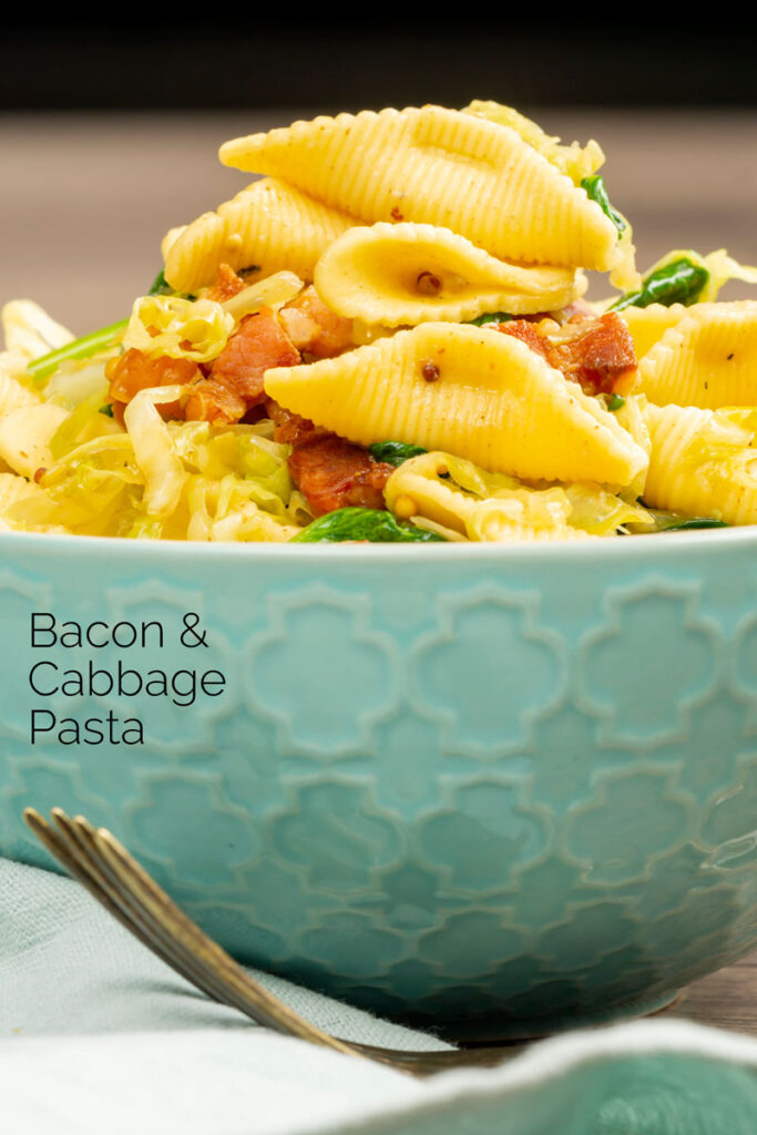 Portrait image of bacon and savoy cabbage pasta served in a baby blue bowl with text overlay