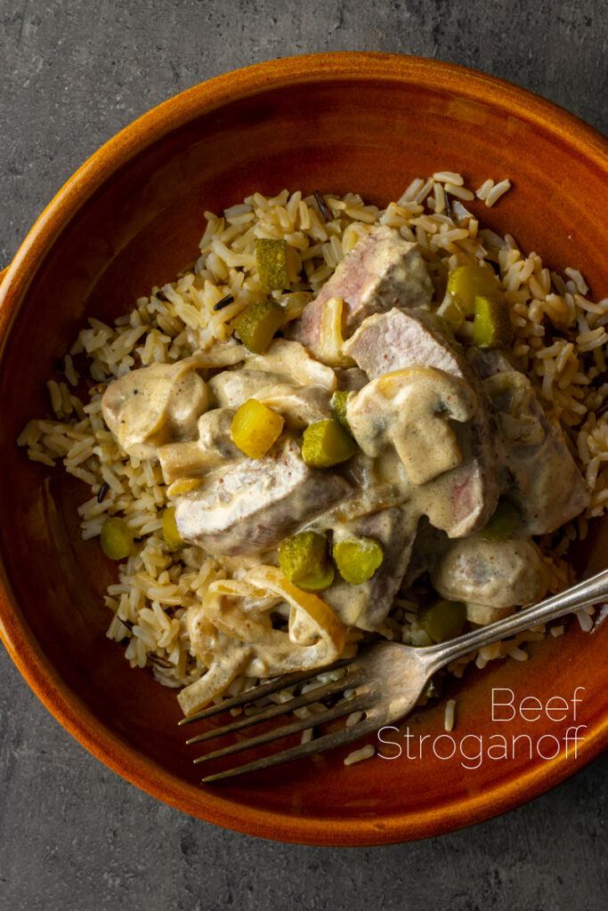 Portrait overhead image of a beef stroganoff with mushrooms served in an earthenware bowl with text overlay