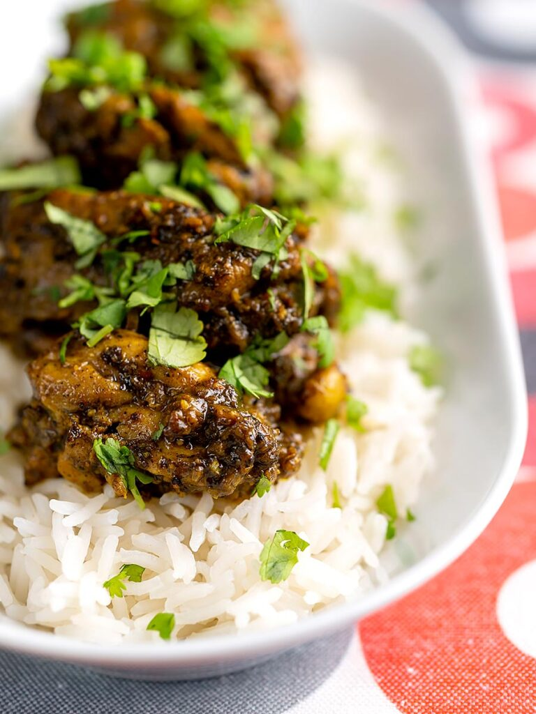 Portrait image of a dry pepper chicken Chettinad curry served on boiled basmati rice.