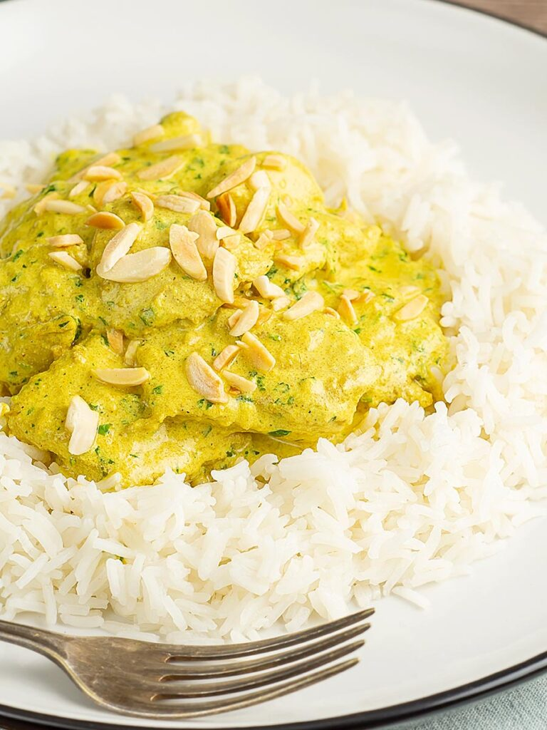 Portrait image of a creamy chicken korma curry served with boiled rice and toasted almonds