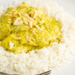 Portrait image of a creamy chicken korma curry served with boiled rice and toasted almonds with a text overlay