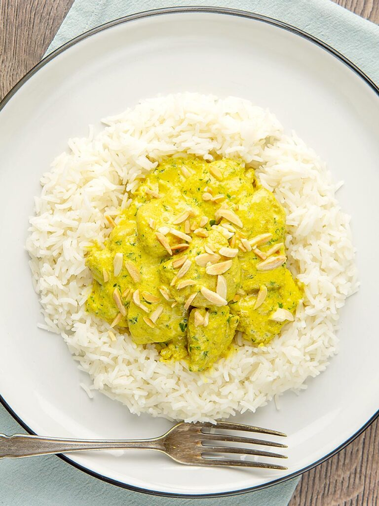Portrait overhead image of a creamy chicken korma curry served with boiled rice and toasted almonds.