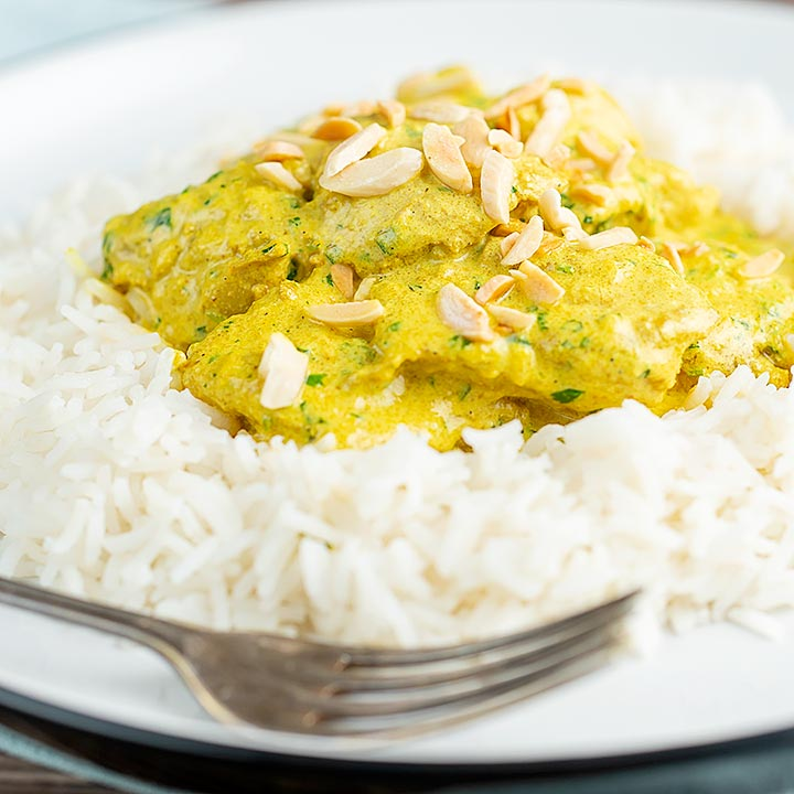 Square image of a creamy chicken korma curry served with boiled rice and toasted almonds.
