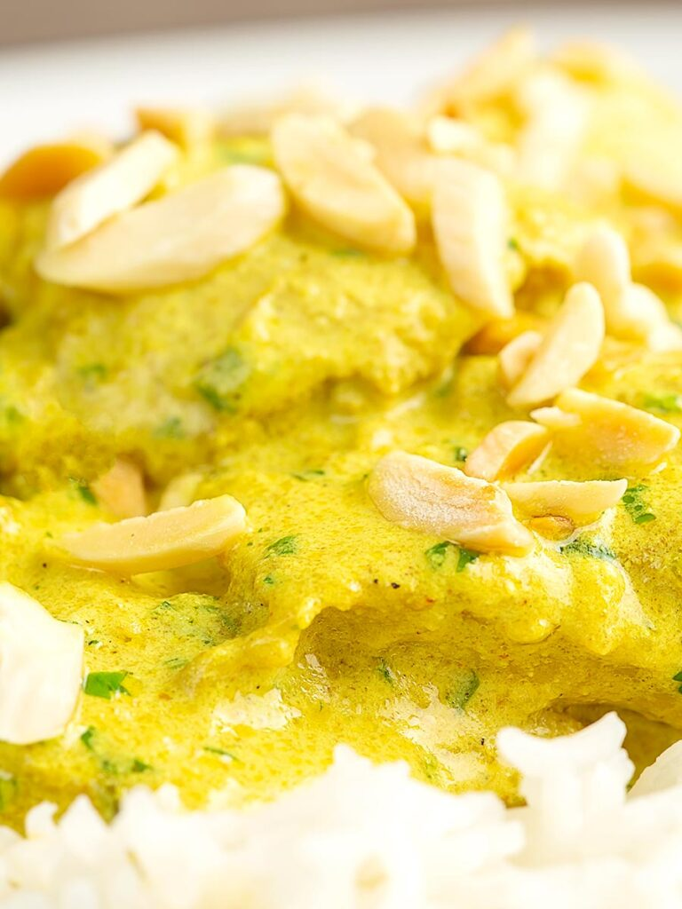 Portrait close up image of a creamy chicken korma curry served with boiled rice and toasted almonds.