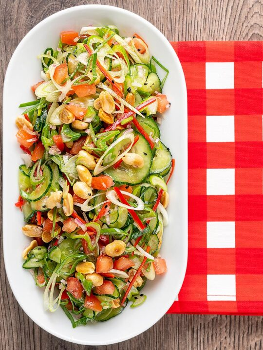 Portrait overhead image of a vibrant cucumber salad featuring chilli, tomatoes, s;ring onion and toasted peanuts