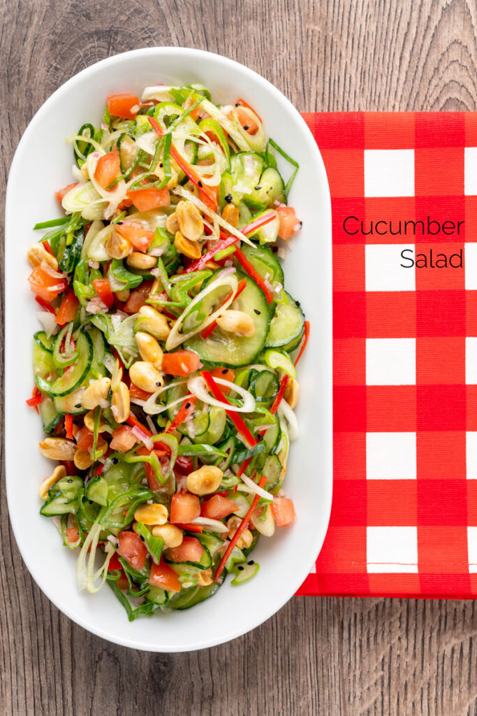 Portrait overhead image of a vibrant cucumber salad featuring chilli, tomatoes, s;ring onion and toasted peanuts with text overlay