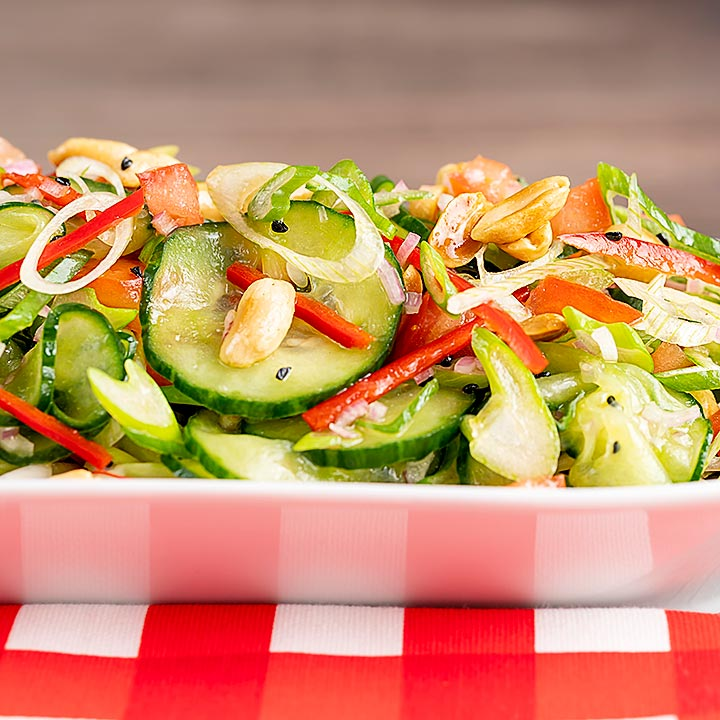 Square image of a vibrant cucumber salad featuring chilli, tomatoes, spring onion and toasted peanuts