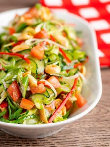 Portrait image of a vibrant cucumber salad featuring chilli, tomatoes, spring onion and toasted peanuts