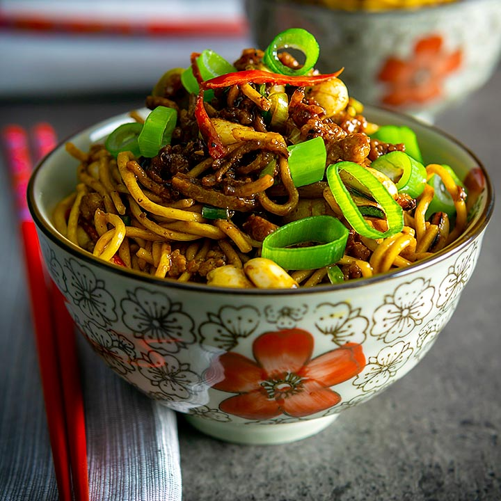 Square image of Dan Dan Noodles served in an Asian style bowl decorated with a red flower